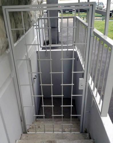 металлическая дверь на лестничную площадку с решеткой